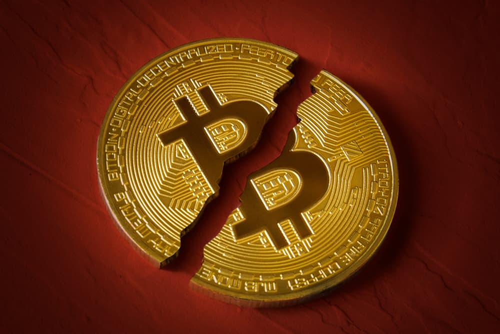 Coin bitcoin is broken in half on red background. The fall and collapse of the course of the crypto currency, the ban on trade, fall down. Source: shutterstock.com