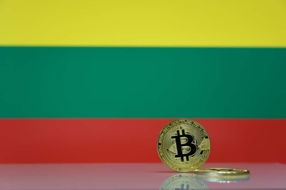 Golden bitcoin stands on a blurred background of state flag of Lithuania. Source: Shutterstock.com