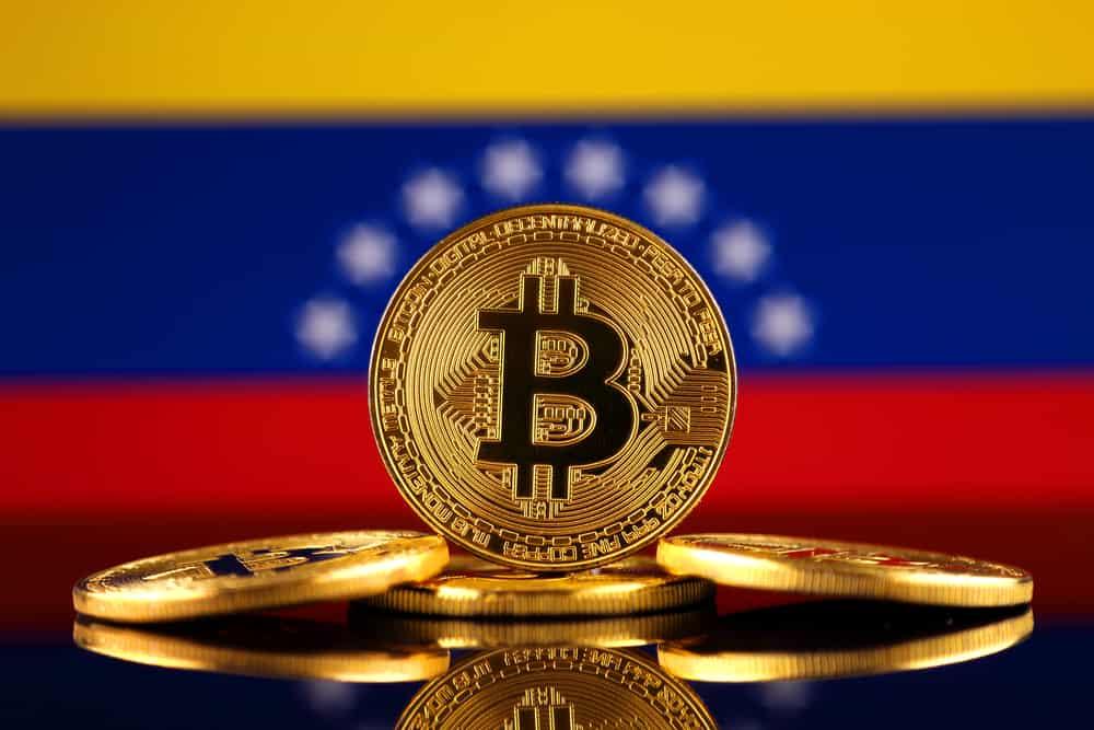 Physical version of Bitcoin (new virtual money) and Venezuela Flag. Source: Shutterstock.com