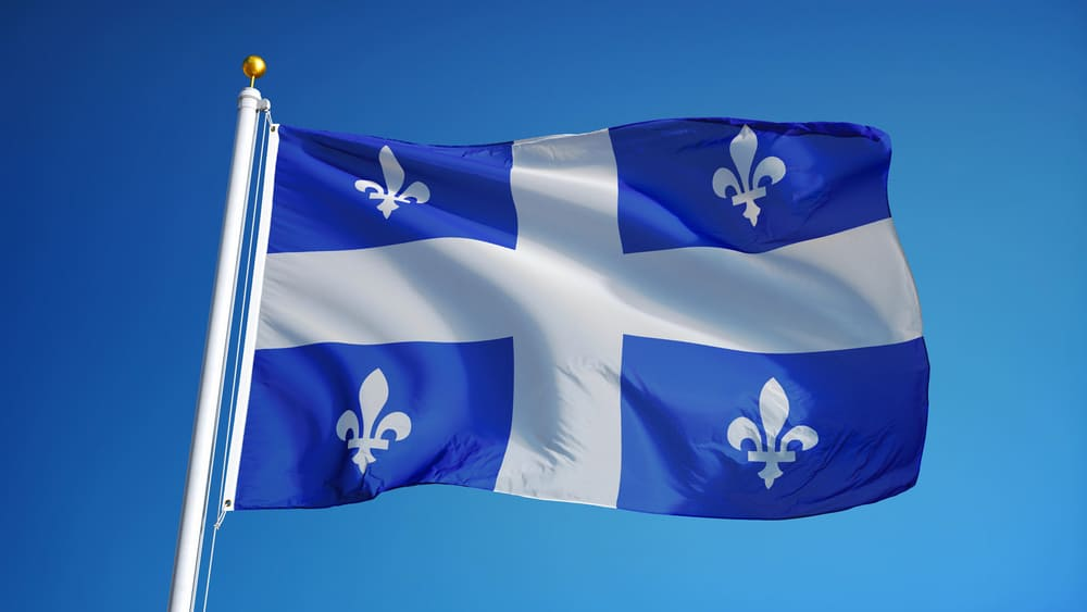 Quebec flag waving against clean blue sky, close up, isolated with clipping path mask alpha channel transparency. Source: Shutterstock.com