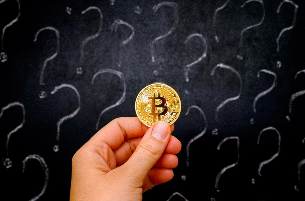 Woman hand with golden Bitcoin virtual money against blackboard with question marks. Source: Shutterstock.com