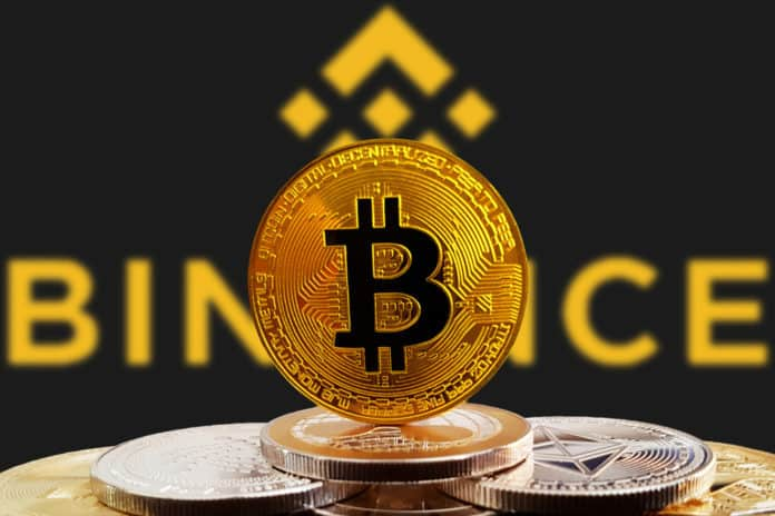 Bitcoin BTC on stack of cryptocurrencies with Binance exchange logo in background. The cryptocurrency coin is golden and in focus. Copenhagen / Denmark - 07 12 2018.