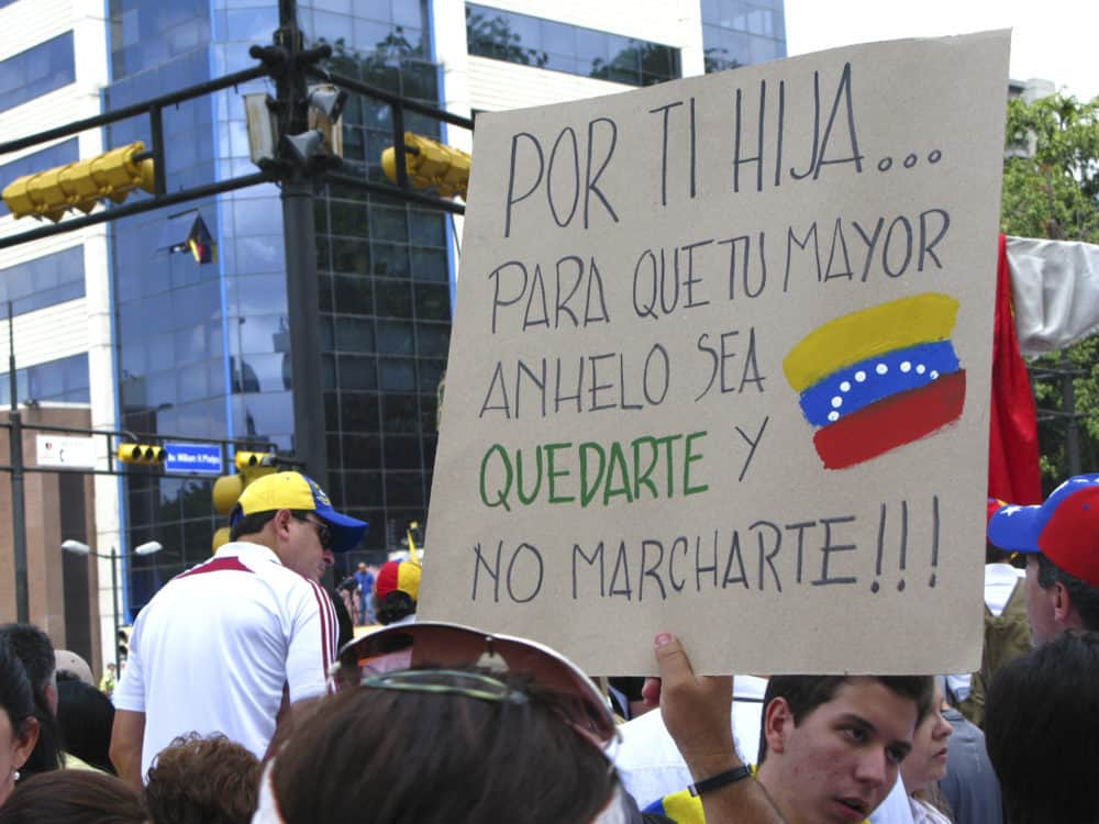 Venezuela: A woman holds a banner demanding the dictatorship to stop the exodus of millions of Venezuelans escaping the chaos caused by the socialist Bolivarian Revolution. Source: shutterstock.com