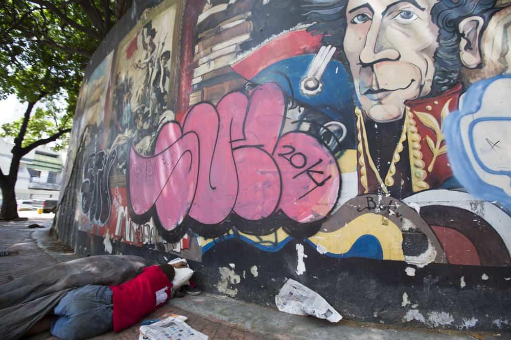 Venezuela: Poor man sleeping on the street of downtown Caracas with a graffiti of Simon Bolivar. Source: shutterstock.com
